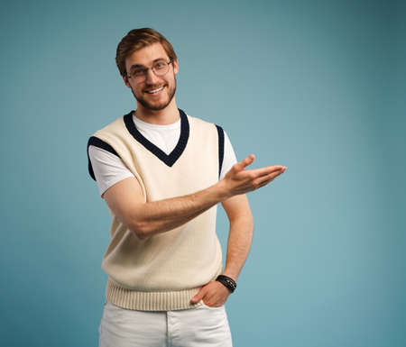 Portrait of a happy young man in casual pointing fingers away at copy space isolated over blue background.
