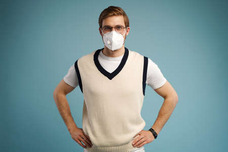 Portrait of handsome young man with surgical medical mask in casual style shirt standing, looking at camera with smile