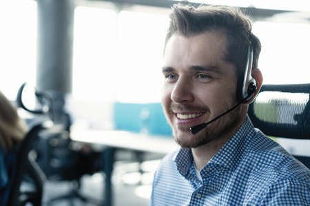 Young handsome male customer support phone operator with headset working in call center Reklamní fotografie
