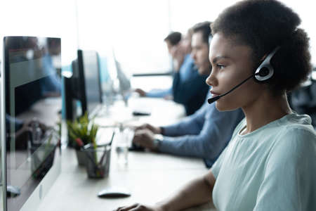How can I help you? Beautiful call center workers in headphones are working at modern office