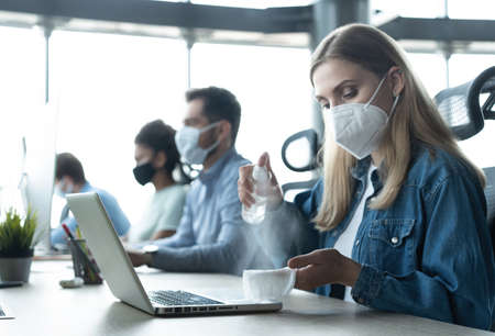 Portrait of young businesspeople with face masks working indoors in office, disinfecting laptop Reklamní fotografie