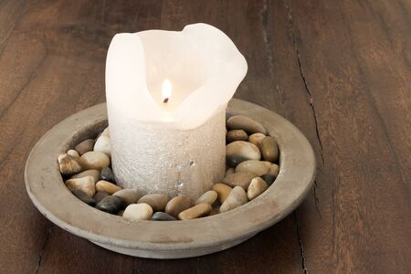 Warm Candle in Stones Setting Stock Photo