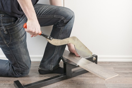 Man Kneeled down to Cut Laminate with Cutter Stock Photo