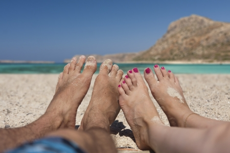 Couple Laying at Sandy Beach Point of View Showing Only Feet