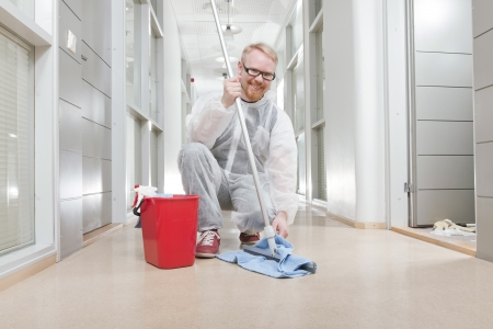Man in Overall Cleaning Office Corridor photo