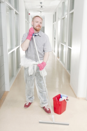 Man Cleaning Corridor with Overall Lowered at Waist