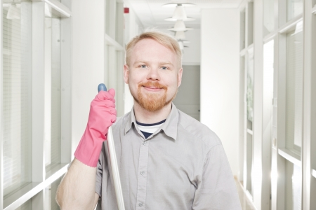 Man Cleaning Corridor and Smiling