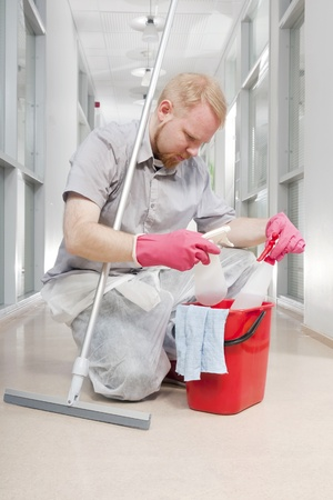Man Kneeled Down over Bucket Comparing Cleaning Detergents Stock Photo