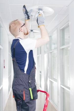 janitor: Man Repairing Broken Light