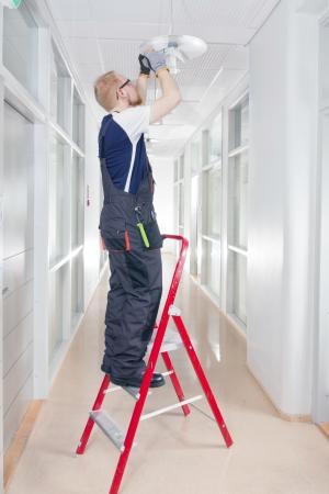Janitor Fixing Broken Lamp 版權商用圖片
