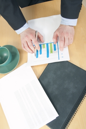 net income: Graph chart and a Folder in Front of Man in Suite