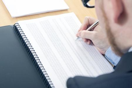Man Highlighting Figures on Data Sheet