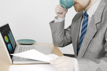Man in Suit Drinking Coffee and Working with Laptop photo