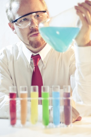 Soft Toned Image of Man Looking at Cyan Liquid in Flask Stock Photo