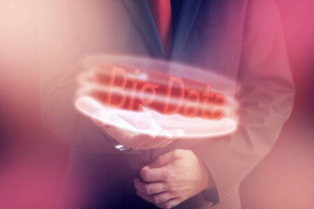 Man in Suit Presenting Three Dimensional Big Data Text in Hand