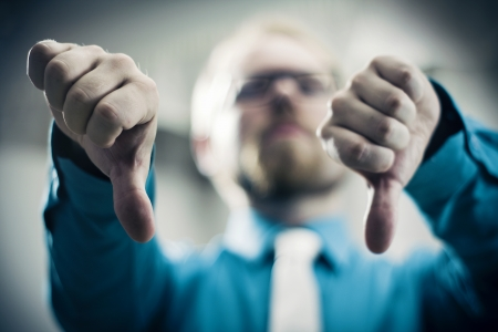 Businessman Showing Thumbs Down Gesture in Strong Toned Image photo