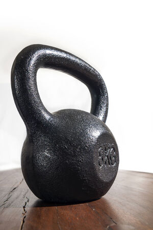 Close-up of 8kg Kettlebell on Wooden Floor photo