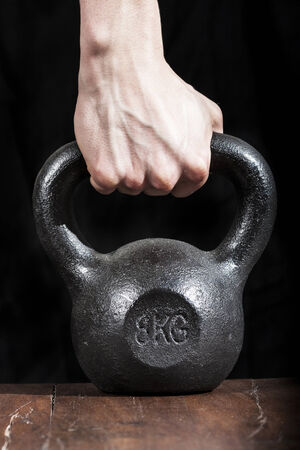 Hand Lifting Black Iron Kettlebell Stock Photo
