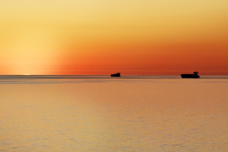 Two Containerships Sailing Towards Setting Sun in Calm Sea