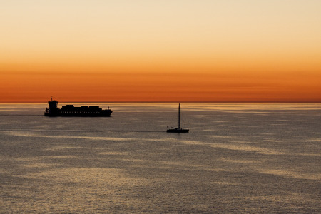 Containership and Sailboat Sailing Together at Dawn Stock Photo