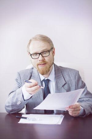 interrogativa: Hombre que sostiene Papers con mirada interrogativa Foto de archivo