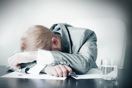 Man Sleeping on Desk at Work
