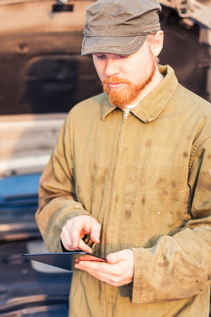 coverall: Man in Dirty Coverall Using Digital Tablet