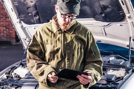 Mechanic Sitting on Hood Reading Tablet