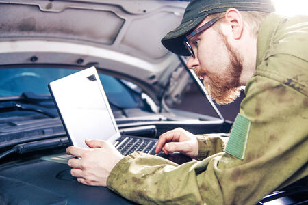 Mechanic Using Laptop on Car Engine