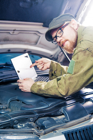 Mechanic Leaning on Car Pointing at Laptop photo