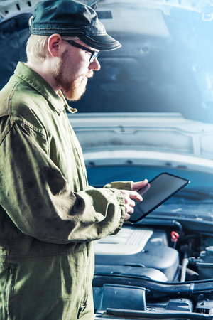 Mechanic Using Digital Tablet in Front of Car