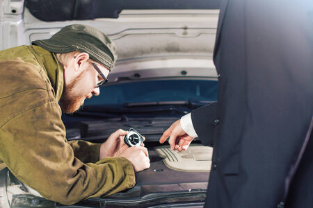 Man in Suit Pointing Motor Oil Slot for Mechanic Stock Photo