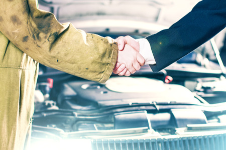 Businessman and Mechanic Handshaking in Front of a Car photo