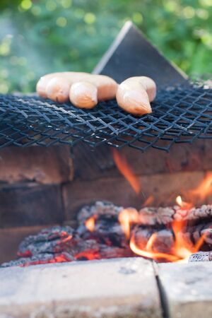 Grilling Sausage on Grill at Fireplace