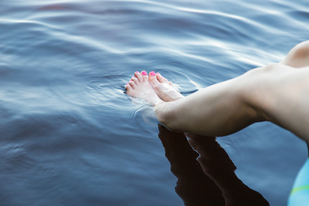 Woman Dipping Feet into Soothing Fresh Water