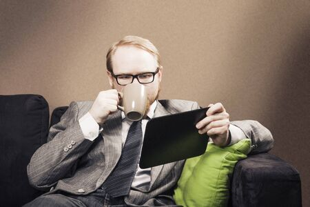Man sitting on Sofa Drinking Coffee and Watching Tablet Computer Screen