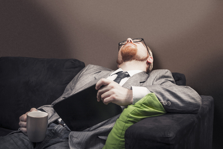 sleeping tablets: Man Fallen Asleep on Home Sofa While Holding Coffee and Tablet