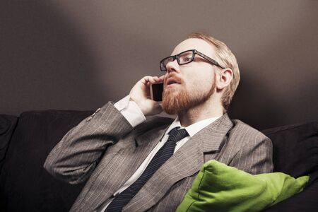 Man In Suit Talking to Cellphone on Home Sofa Stock Photo