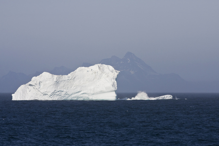 Iceberg Floating in Ocean with Mountains in the Background Stock Photo