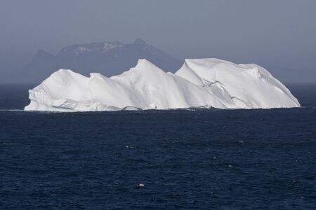 Iceberg Floating in Ocean with Mountains in the Background 스톡 콘텐츠