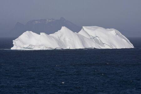 Iceberg Floating in Oceaan met bergen op de achtergrond