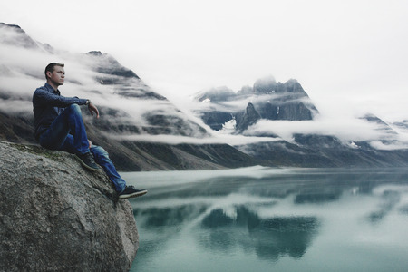 Man Sitting on a Cliff, Watching Mountains Becoming Covered with Clouds