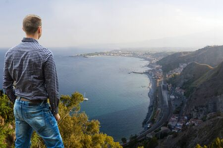 Man Standing High Looking Far into Distance along Mediterranean Coastline in Sicily  Stock Photo