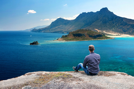 Young Man Sitting High on Mountain Ledge and Enjoying the View Stock Photo