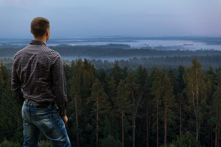 Standing Man Looking at Rising Mist in the Woods Stock Photo