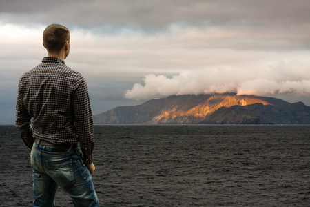 Standing Young Man Looking at Mountains Across the Sea  Stock Photo