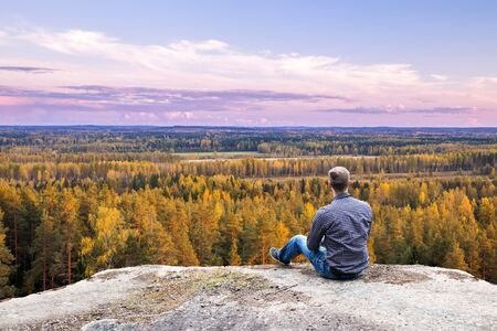Young Man Sitting on High Hill and Watching Horizon