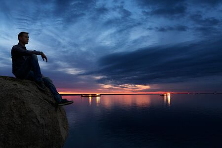 Man Sitting on a Cliff Watching Sea and Ships at Anchor Stock Photo