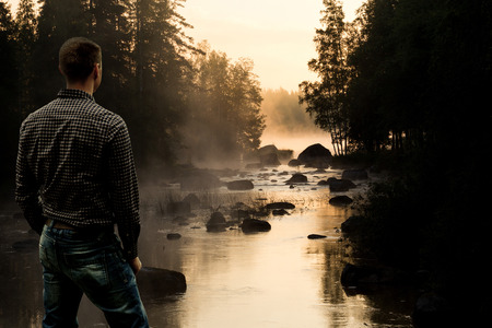 Young Man looking at Stream in Setting Sun