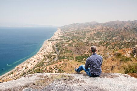 Young Man Sitting on a High Hill and Enjoying the View in Sicily
